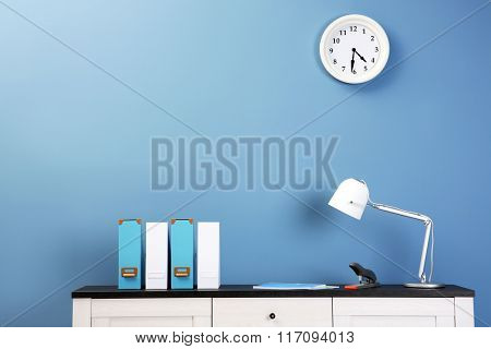 Wooden chest of drawers with folders, lamp and stapler on blue wall background