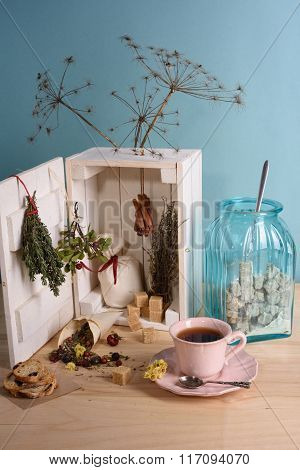 Herbal tea in vintage cup. Wooden box filled with herbs, spices and sugar. Turquoise background.