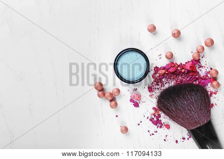 Makeup brush with cosmetics on a white background