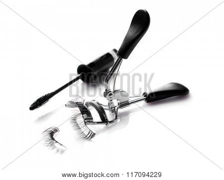Curler, mascara brush and false eyelashes, isolated on white