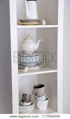 Different clean dishes on wooden shelves