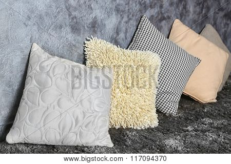 Few pillows on grey wall background