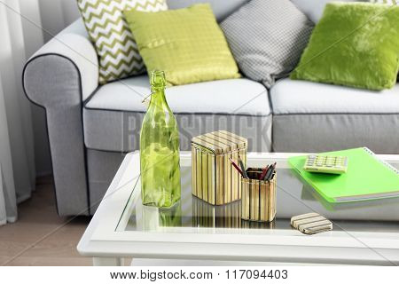 Low table with notebooks and green bottle in living room