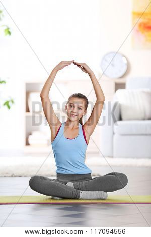 Young girl making fitness exercise indoors