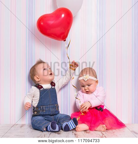 Baby boy and girl playing with heart balloons for valentines day