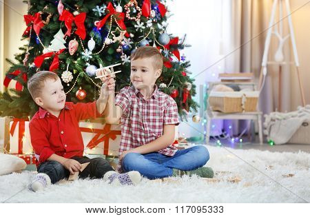 Two cute small brothers playing with wooden plane on Christmas tree background