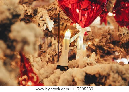Candles with red balloon on a snowy branch