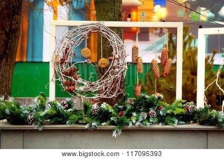 Table decorated with Christmas tree branches and wreath of twigs outdoors