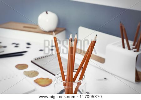 Set of pencils in glass jar on a table