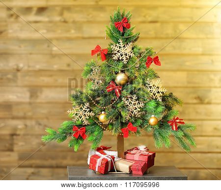 A handmade green Christmas tree and presents on wooden wall background