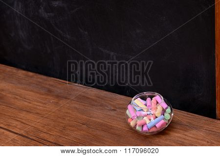 Glass jar with coloured chalk on desk in front of blackboard