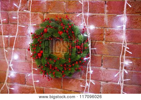 Christmas wreath and lights on the wall background