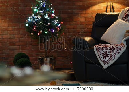 Living room interior with black armchair and Christmas tree on brick wall background