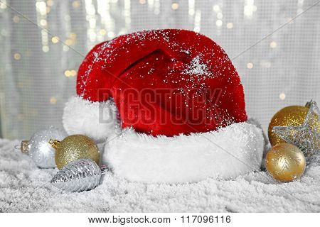 Santa Claus hat with toys on a snowy table over glitter background