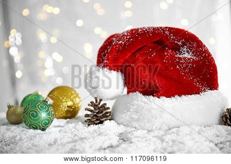 Santa Claus hat with baubles and cones on a snowy table over glitter background