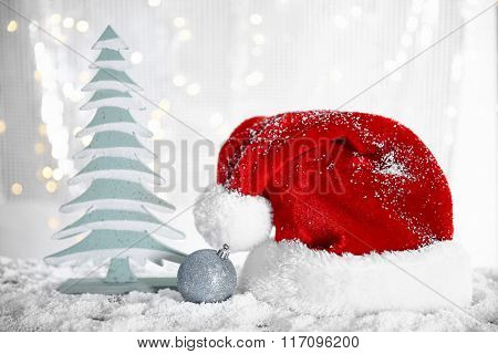 Santa Claus hat with bauble and fir tree on a snowy table over glitter background