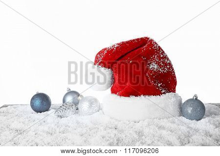 Santa Claus hat with toys on a snowy table over white background