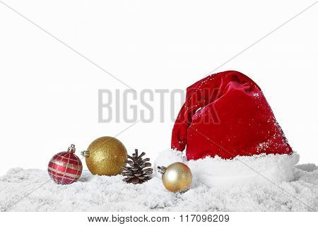 Santa Claus hat with baubles and cone on a snowy table over white background