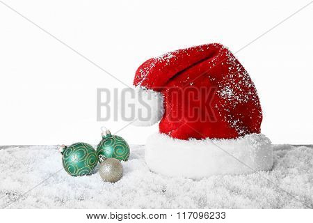Santa Claus hat with baubles on a snowy table over white background