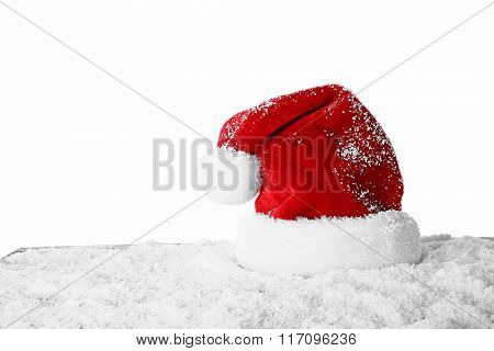 Santa Claus hat on a snowy table over white background