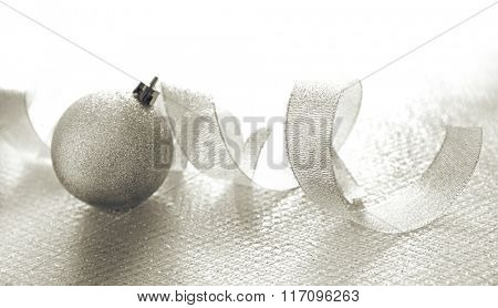 Silver curly ribbon with decorative baubles on shiny background