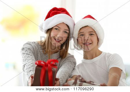 Portrait of girl and boy with gifts in decorated Christmas room