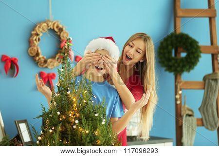 Boy decorates Christmas tree, while girl closing his eyes, close up