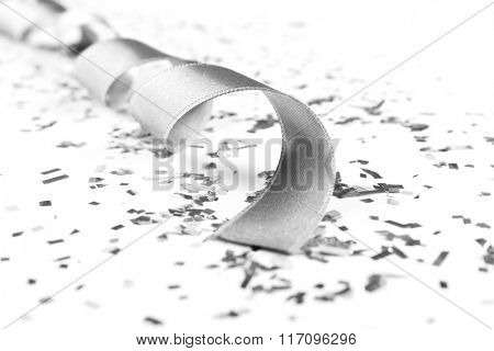 Silver curly ribbon on shiny background