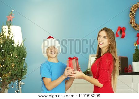 Girl presents gift to boy in decorated Christmas room
