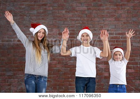 Boys and girl with hands up on brick wall background