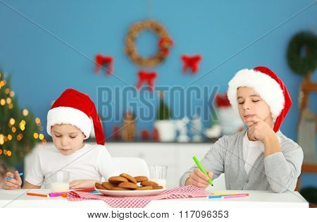 Cheerful boys painting with crayons in decorated Christmas room
