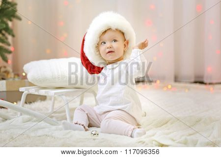 Funny baby girl wearing red hat in Christmas living room