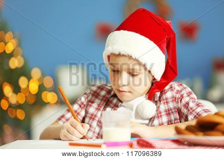 Cheerful boy writing a letter to Santa Claus, close up
