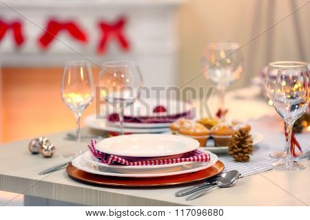 Christmas table setting with holiday decorations on fireplace background