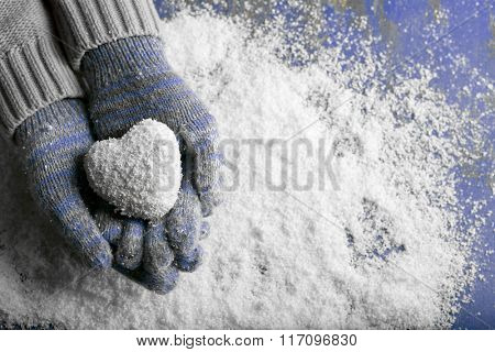 Female hands in mittens with snow heart on snow background