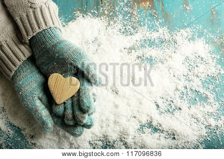 Female hands in mittens with wooden heart on snow background