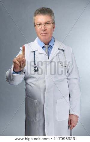 A handsome doctor pointing with finger, on grey background
