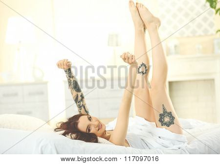 Attractive woman with tattoo raising her hands and legs on the bed