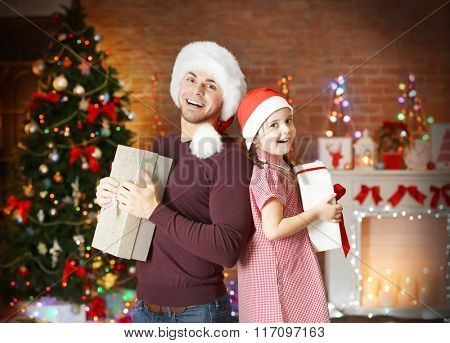 Older brother and little sister in Santa hat with gift  on Christmas background
