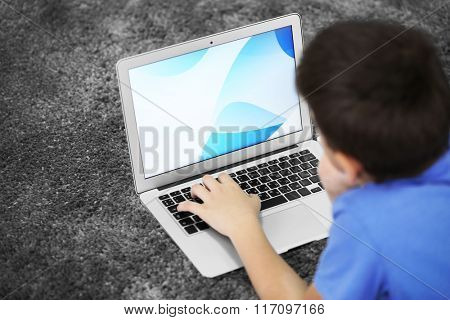 Little boy using laptop on a floor at home, close up