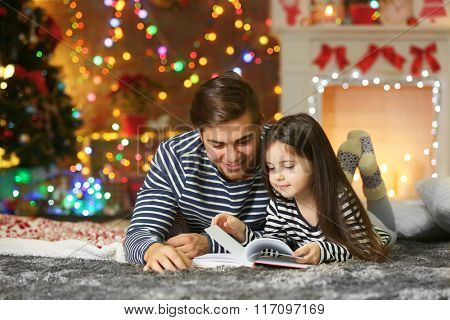 Older brother with little sister reading book in Christmas living room