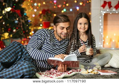 Older brother with little sister reading book and eating cookies in Christmas living room
