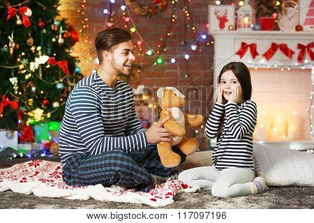 Older brother giving little sister a Teddy bear in Christmas living room