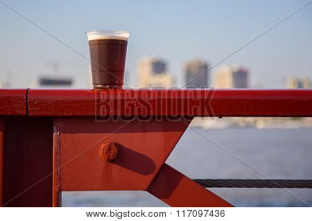 Glass Of Dark Beer On A Handrail
