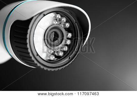 Security CCTV camera on grey background, closeup