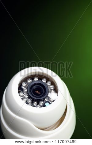 Security CCTV camera on green background, closeup