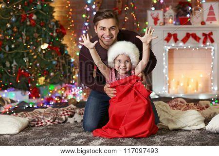Funny little sister in Santa sack surprising her older brother on Christmas background
