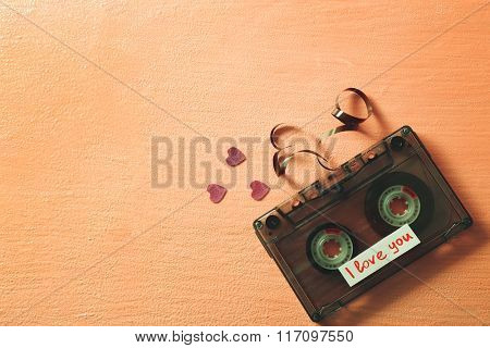 Retro audio cassette with tape in shape of heart on pink textured background