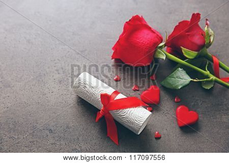 Red roses with rolled present card on grey textured background