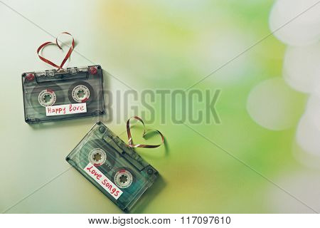 Retro audio cassettes with tapes in shape of hearts on green blurred background